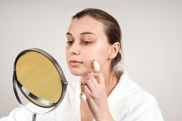 A beautiful young woman in a white robe uses a jade roll to massage her face, looks in the mirror
