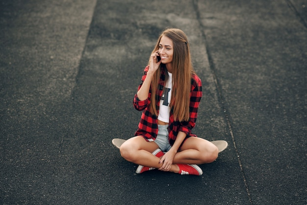 Beautiful young woman in a white shirt, red shirt, shorts and sneakers, sitting on a skateboard and talking on the mobile phone