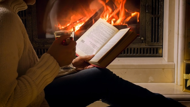 Beautiful young woman in white sweater drinking tea and reading book at fireplace