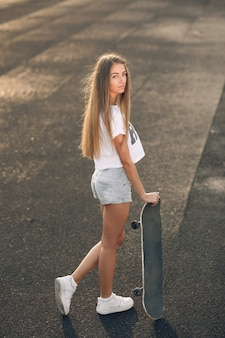 Beautiful young woman in a white t-shirt, shorts and white sneakers standing with skateboard in hands