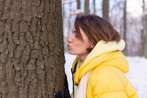 Beautiful young woman in the winter forest shows tender feelings for nature, shows her love for the tree