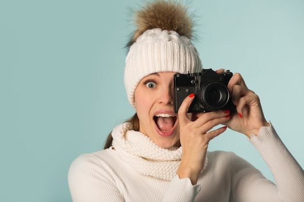 Beautiful young woman in winter hat with a camera in hand on a blue background