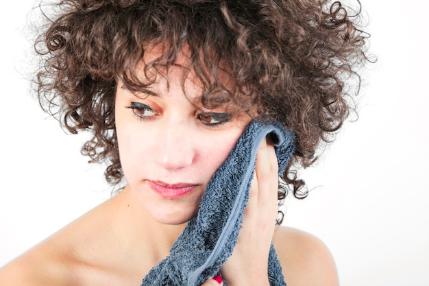Beautiful young woman wipes her face with towel isolated over white background