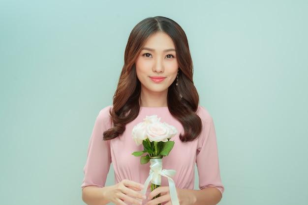 밝은 배경에 장미 꽃다발을 든 아름다운 젊은 여성
