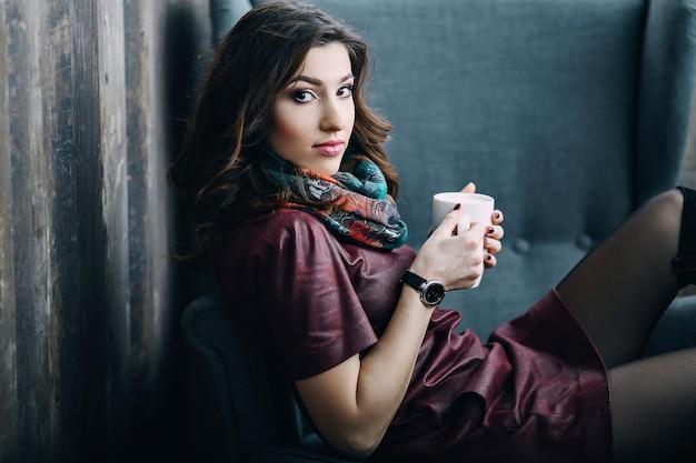 カフェでお茶やコーヒーを飲む美しい若い女性、ホットビバレッジのカップを持つ美容モデルの女性。温かみのある色調の、お茶を飲みながらカフェに座っているかなり若い女性