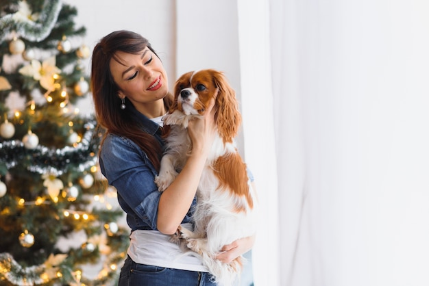 クリスマスツリーの近くで犬と美しい若い女性