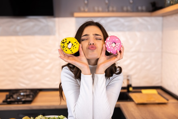 手にドーナツを持つ美しい若い女性。台所のテーブルの上の女の子。
