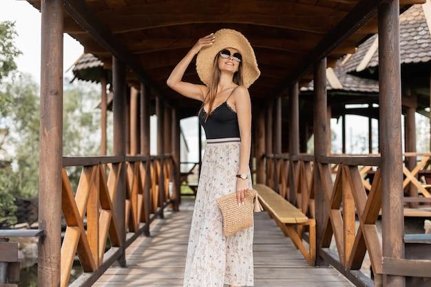 세련된 밀짚 모자와 고리버들 가방을 여름 빈티지 드레스에 넣은 아름다운 젊은 여성이 해변 근처의 나무 부두를 걷는다