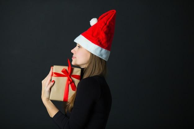 黒の背景に贈り物を手に美しい若い女性