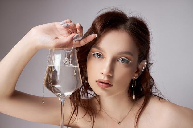 유리와 그녀의 손에 보석 아름 다운 젊은 여자. 전문 메이크업, 표현력있는 눈