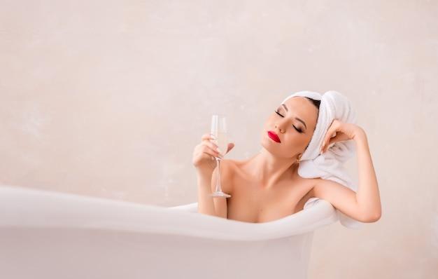 Красивая молодая женщина с бокалом шампанского в ванной комнате. девушка с полотенцем на голове отдыхает в светлой ванной. место для текста