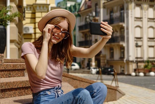 Красивая молодая женщина в шляпе, делающая селфи