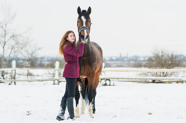 눈에 겨울에 자연에 말과 함께 아름 다운 젊은 여자