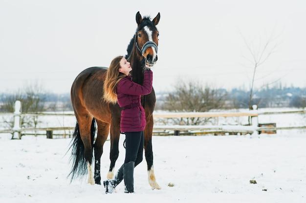 Красивая молодая женщина с лошадью на природе зимой на снегу