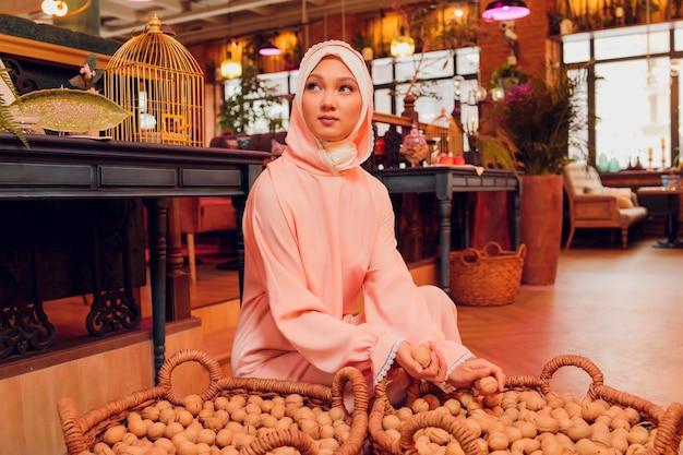 분홍색 hijab와 아름 다운 젊은 여자.