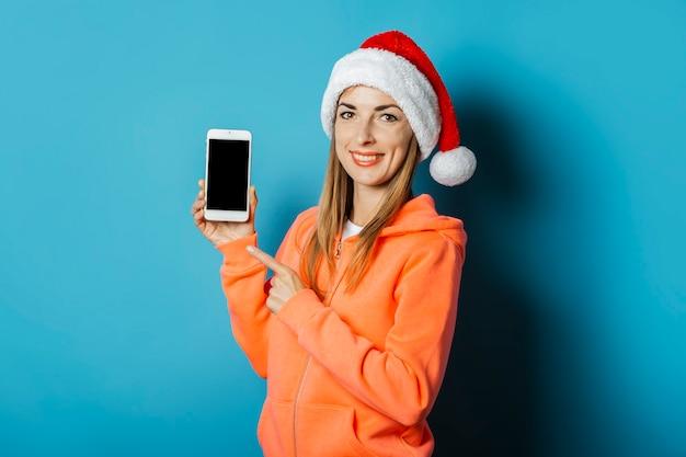까마귀와 산타 클로스의 모자에 미소를 가진 아름 다운 젊은 여자는 휴대 전화를 보유하고