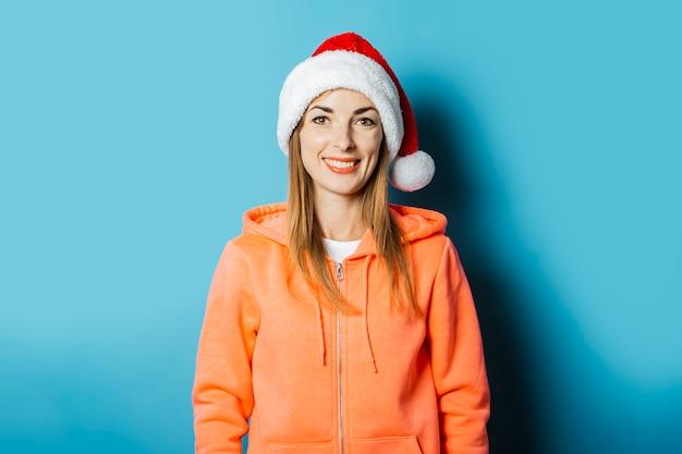까마귀에 미소와 산타 클로스의 모자와 함께 아름 다운 젊은 여자
