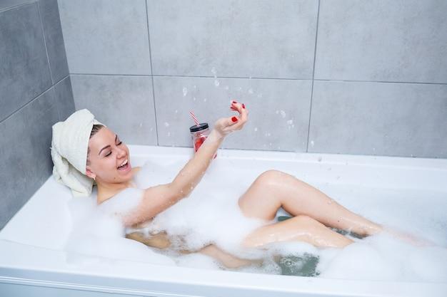 カクテルを飲みながら頭にタオルを持った美しい若い女性が家でお風呂に入ります。忙しい一日を過ごした後はリラックスしてください。スパはリラックスできる手順です。