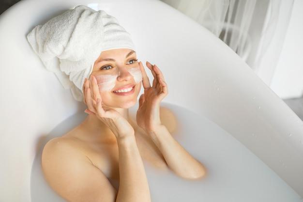 牛乳風呂で頭にタオルを持った美しい若い女性