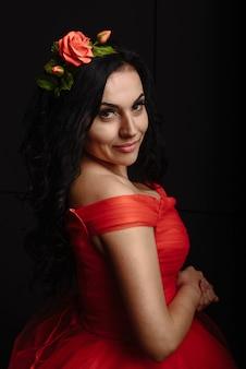 黒の豪華な夜の赤いドレスにバラの花輪を持つ美しい若い女性