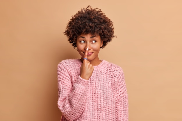 Beautiful young woman with afro hair points at nose with index finger has glad expression foolishes around and looks away dressed in knitted sweater isolated over brown wall