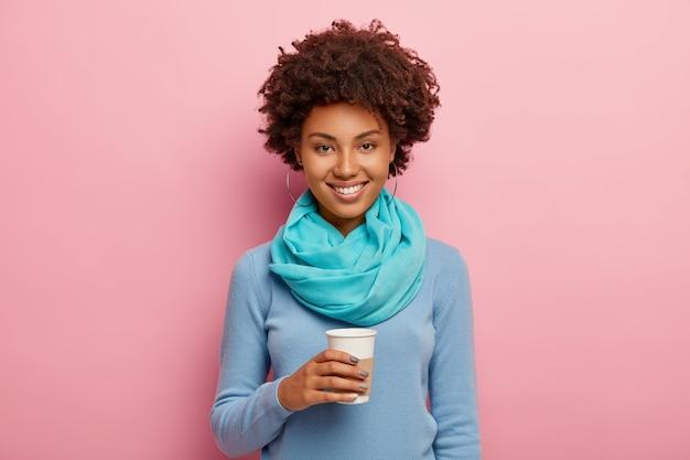 Bella giovane donna con l'acconciatura afro, tiene una tazza di caffè usa e getta, vestita con un maglione blu, guarda volentieri, ha un umore felice