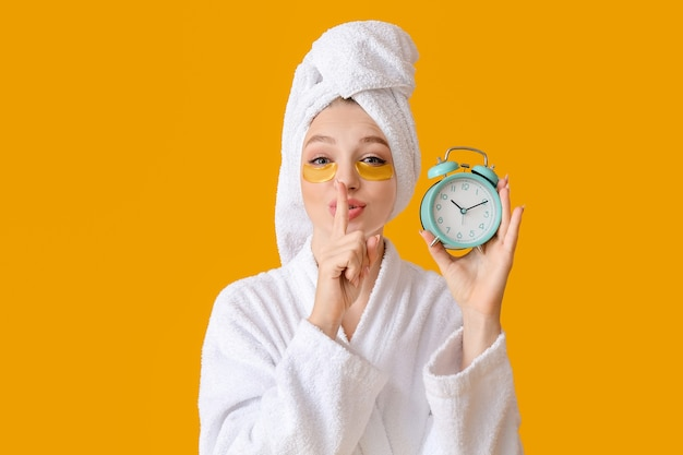 Beautiful young woman with alarm clock showing silence gesture on color surface