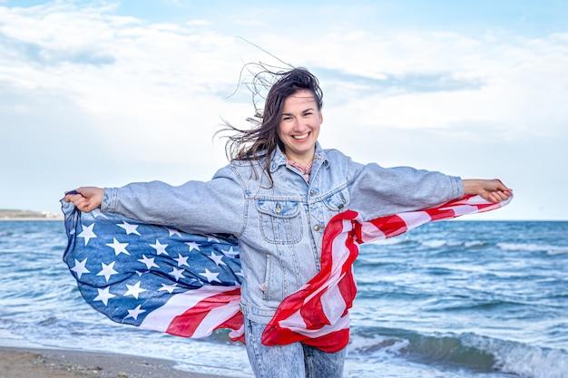 Красивая молодая женщина с американским флагом на берегу моря. концепция патриотизма и празднования дня независимости.