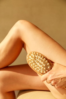 Beautiful young woman with anti cellulite massage brush