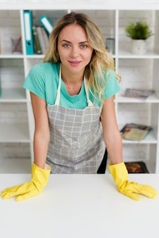 Beautiful young woman with apron and yellow glove looking at camera