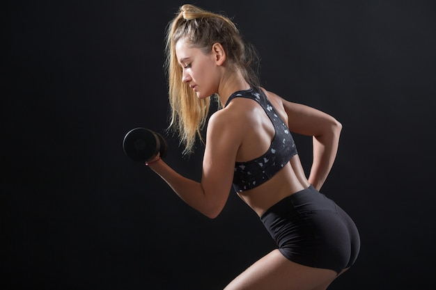 Beautiful young woman with an athletic figure on a black background
