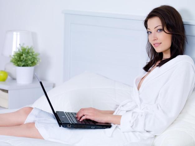 Красивая молодая женщина с привлекательной улыбкой, используя ноутбук в спальне - в помещении
