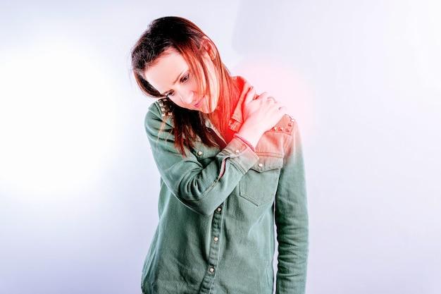 Красивая молодая женщина с болью в спине в шейном отделе на белом телефоне с красной зоной. боль в спине и концепция ухода. потребность физиотерапевта