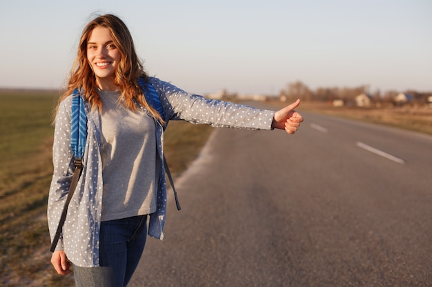 Beautiful young woman with backpack hitchhikes along road, keeps thumb raised, has delighted expression, has vacation trip. pretty female waits for cars on asphlt road, explores new destination