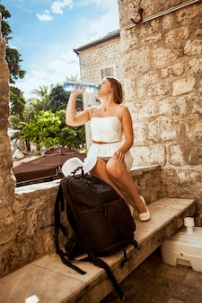 Beautiful young woman with backpack sitting in shadow on street and drinking water