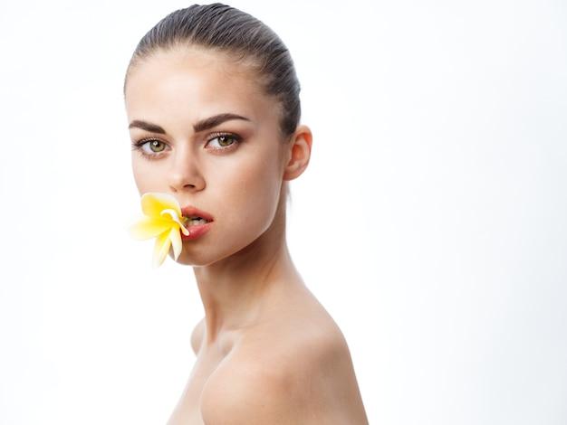 裸の肩と彼女の歯に花を持っている美しい若い女性