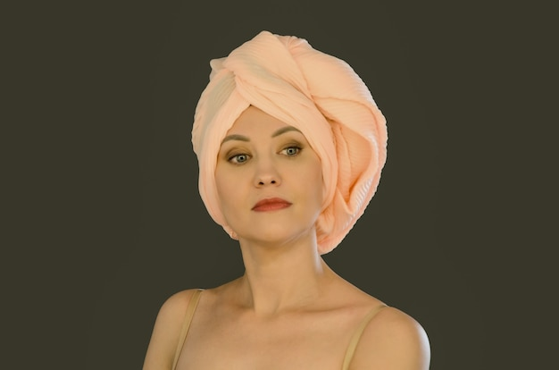 暗い壁にターバンの形で結ばれた桃のスカーフで彼女の頭に裸の肩を持つ美しい若い女性
