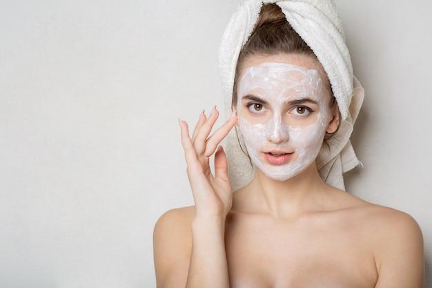 彼女の顔に保湿マスクを使用して頭にバスタオルを持つ美しい若い女性。自宅でのパーソナルケアのコンセプト。テキスト用のスペース