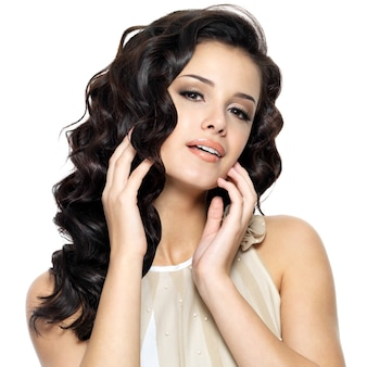 長い巻き毛の美しさを持つ美しい若い女性。白い背景で隔離のファッションモデルの肖像画