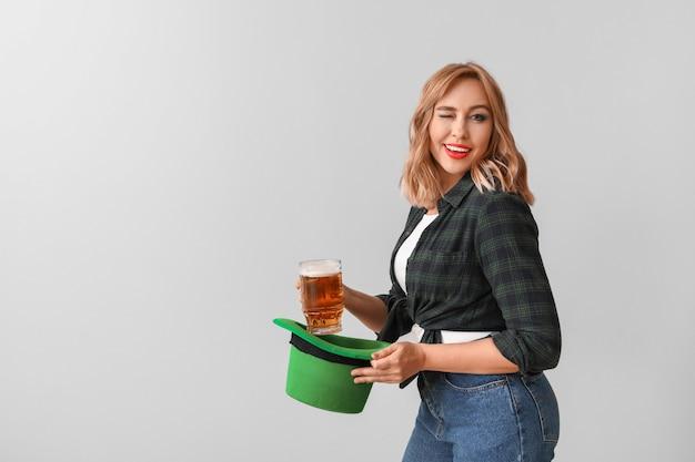 明るい背景にビールと美しい若い女性。聖パトリックの日のお祝い