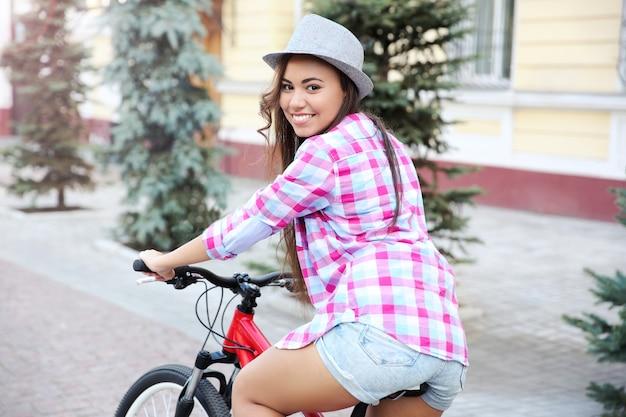 路上で自転車を持つ美しい若い女性