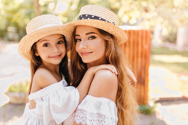 驚いた表情で見ている娘を保持している大きな緑色の目を持つ美しい若い女性。日当たりの良い公園の周りに子供を運ぶきれいな女性のクローズアップ屋外写真。