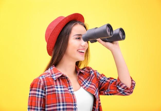 Красивая молодая женщина с биноклем на цветном фоне