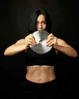 Beautiful young woman with black hair and a sports figure holds a steel circle for sports