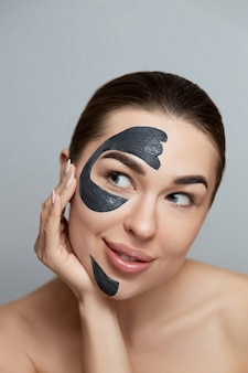 Beautiful young woman with black mask of clay on face clean fresh skin . girl beauty face care. facial treatment . purifying moisturizer mask