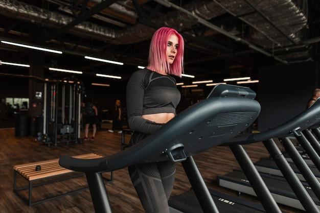 Красивая молодая женщина с черной стильной спортивной одеждой работает на беговой дорожке в тренажерном зале