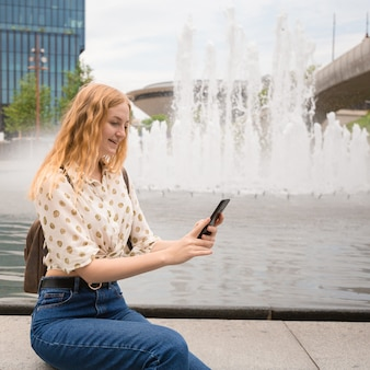 Красивая молодая женщина с сообщениями светлых волос на смартфоне возле фонтана.