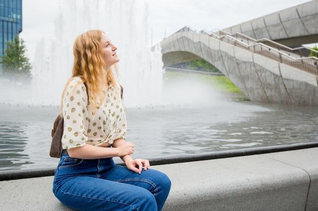 噴水の近くに立っているブロンドの髪と美しい若い女性。女の子は晴れた日に通りでリラックスします。旅行とアクティブな生活の概念。屋外