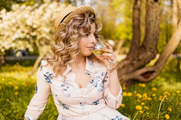 Beautiful young woman with blonde hair in straw hat drinks wine and sitting on the plaid in the garden during a summer picnic