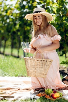 Beautiful young woman with blonde hair in straw hat and pink dress sitting on the plaid in the grape garden